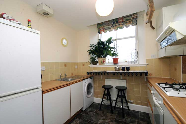 Waterside Property - 2 Bedroom Flatfor sale Kitchen - Fitted kitchen. Photo shows fridge freezer, washer dryer and mosaic breakfast bar.