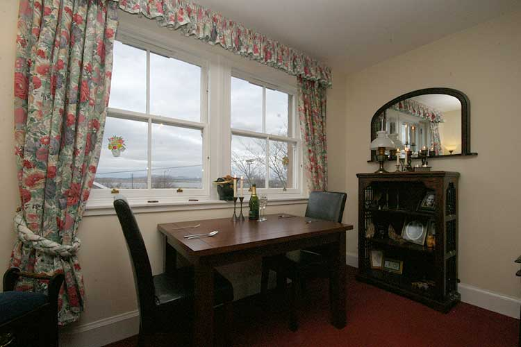 Waterside Property - 2 Bedroom Flatfor sale Dining Area - This is the dining area containing a 4 person dining table. Views from this window are over the steam railway line, communal land on the river front, the Forth, and Fife beyond.